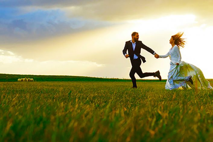 Bride and groom running down green pasture in rural